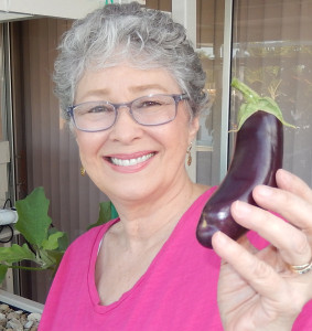 Phyllis Davis, Co-Inventor, Portable Farms harvesting her first eggplant from Portable Farms.