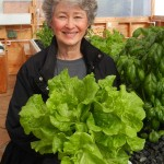 Phyllis Davis holding one head of bib lettuce from in Portable Farms®.