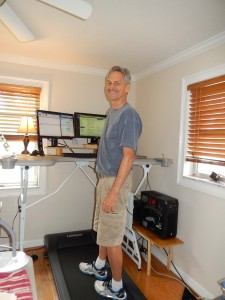 Colle working at his new standing desk and walking on treadmill underfoot while working.