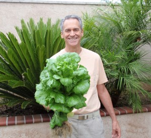 "The Happy Portable Farmer, Colle Davis (aka The Fish Whisperer), Inventor, with a single head of lettuce from one of his own Portable Farmsâ""¢ Aquaponics Systems that was grown in only 40 days. This is an unretouched photo."